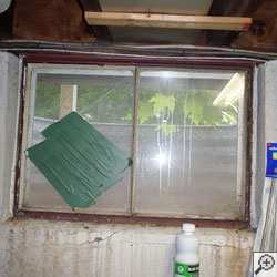 An old, rusted basement window with a steel frame.