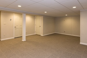 Finished basement space with waterproof wall paneling, ceiling tiles and floor system
