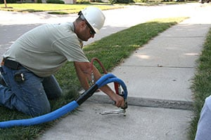 Technician raising sidewalk with PolyLevel® in Staten Island